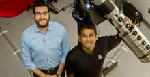 Vishnu Reddy, right, and Tanner Campbell stand next to the RAPTORS telescope at the UA's Kuiper Space Sciences building. They would like to mount an optical sensor system on the telescope in the future. (Photo: Mari Cleven/UA Research, Discovery & Innovation)
