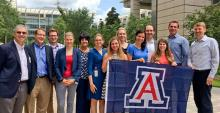 A group of people posing together with a UA flag