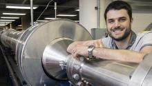 Alex Craig smiles and rests his arm on a 104-foot silver wind tunnel.