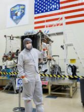 Bradley Williams with the OSIRIS-REx spacecraft in the Lockheed Martin cleanroom. Photo by Symeon Platts/The University of Arizona