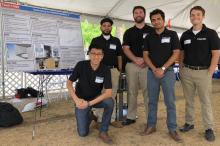 Five male students wearing black polo shirts stand before a poster explaining their Design Day capstone project.