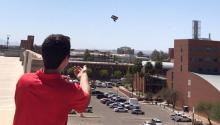 A student sends a balloon off a building