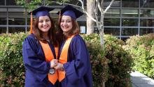 Two women stand in a courtyard, wearing graduation robes and hats, holding hands.