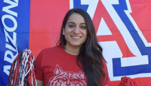 Maira Garcia standing in front of the University of Arizona logo