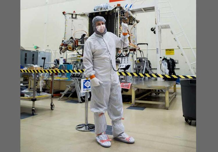 Bradley Williams, a University of Arizona alumnus and employee, and recent recipient of a 2019 Flinn-Brown Fellowship, poses with the OSIRIS-REx spacecraft in the Lockheed Martin cleanroom.