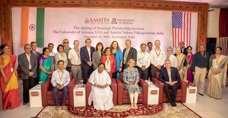 "Approximately 30 people sit and stand in front of a banner reading ""The signing of Strategic Partnership between The University of Arizona and Amrita Vishwa Vidyapeetham, December 12, 2019, Amritapuri, India"""