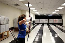 Sophomore Madison Eich aims at a target at the PSE Archery range. Photo by Darien Bakas / The Daily Wildcat