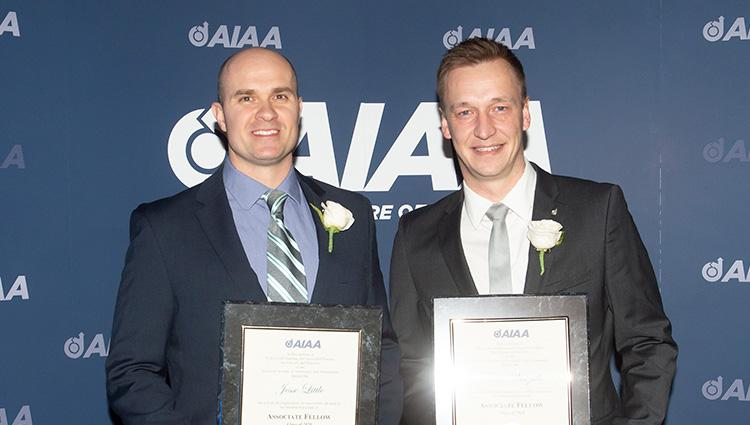 Two men in dark suits stand in front of an AIAA-branded background. They are holding their associate fellow certificates.
