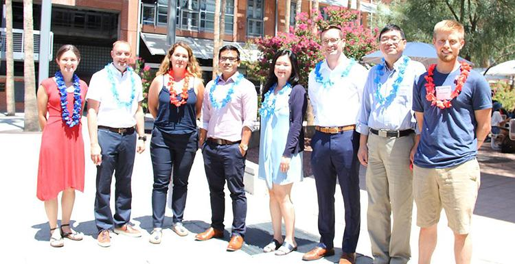 Eight new engineering faculty members stand in the AME courtyard wearing festive leis