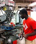 Engineering senior Rolland Prempeh perfects a component for his senior design project on a mill in the AME machine shop