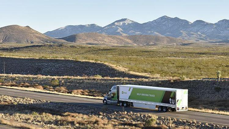 A TuSimple truck on a flat highway in the desert, with mountains in the distance.
